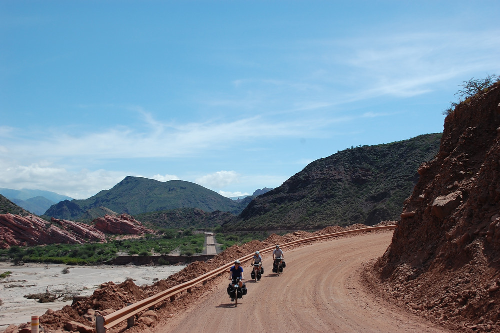 Three cyclists riding down a red gravel road next to a river in the mountains against a blue sky