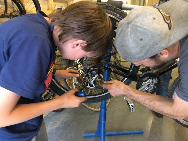 Older boy helping a younger boy fix a bike