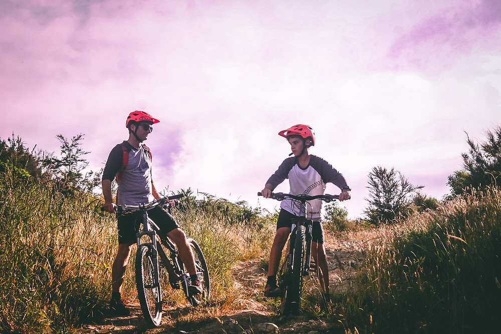 Two males of different ages in red helmets sitting on their bicycles on a trail