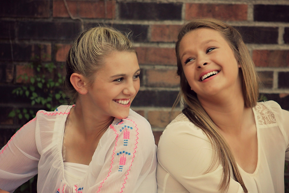 Two blond girls sitting next to each other wearing white shirts and smiling