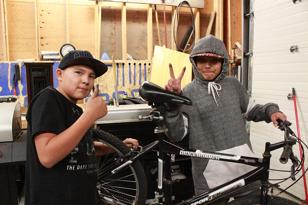 Two young men with a bike showing the peace sign and a thumbs up