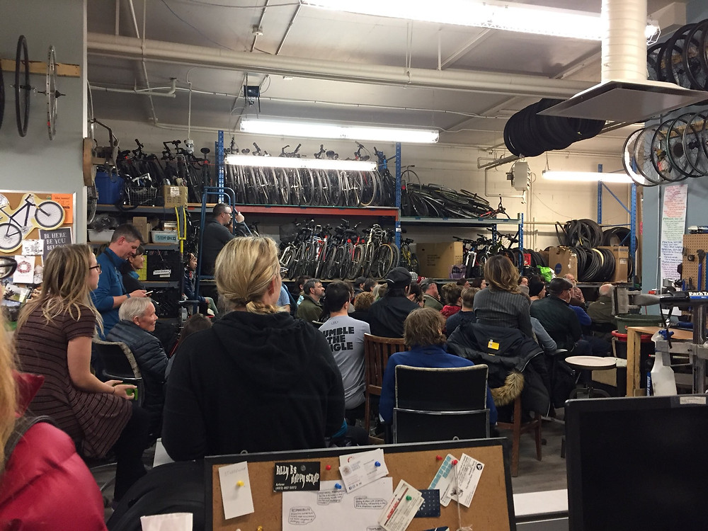 A group of people in a large room with bicycles, listening to a speaker
