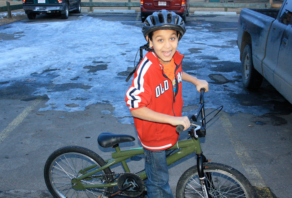 Young boy in a red top smiling while holding a green bicycle