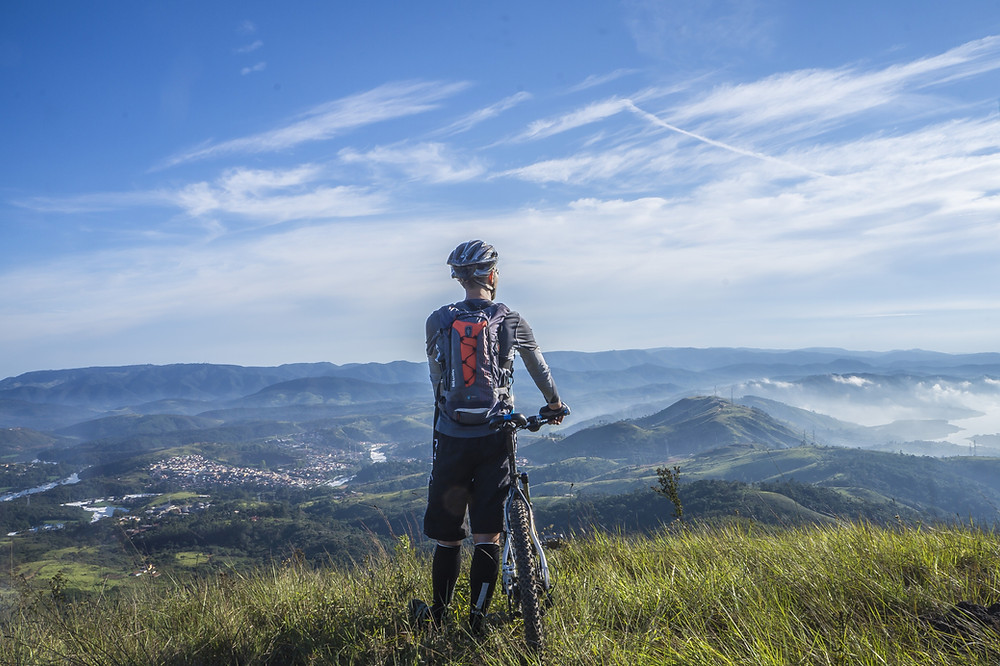 Man standing with his bike looking out at the mountain range in front of him