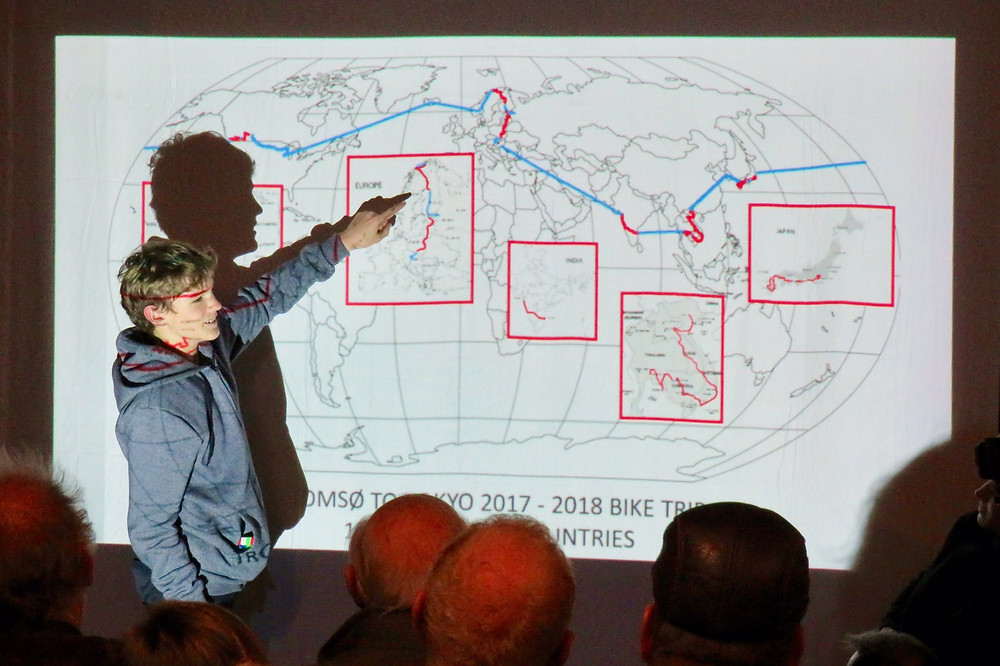 A young man points to a map on a projector screen, showing the route his family took on a round the world bike trip