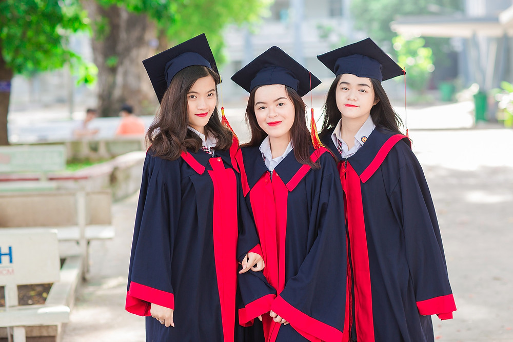 3 Asian girls in graduation cap and gowns