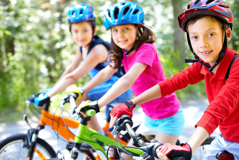 Three young kids wearing brightly coloured clothes riding bikes