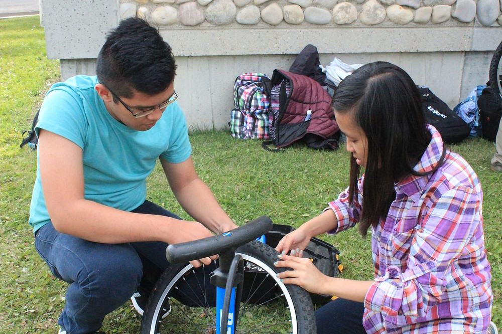Two young people fixing a bicycle tire