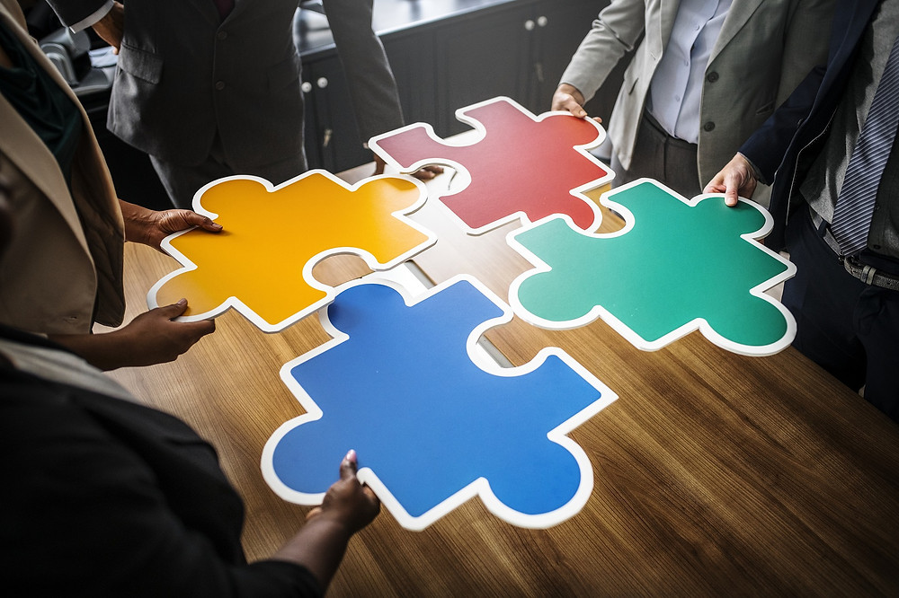 People's hands holding multi-coloured large puzzle pieces