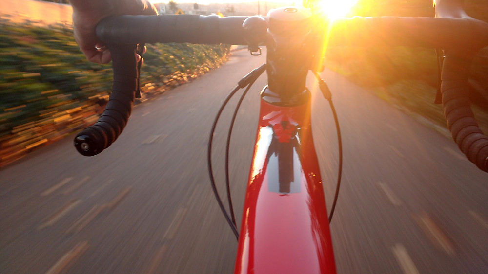Red bicycle riding into the sun