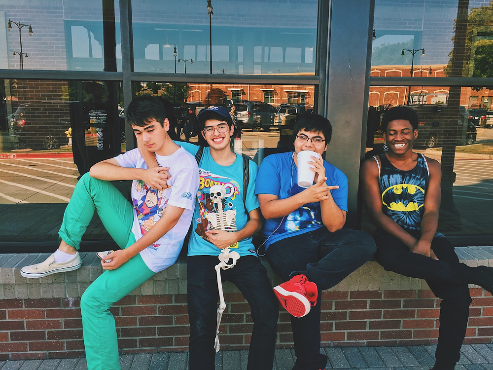Four young men sat on a ledge outside a building window
