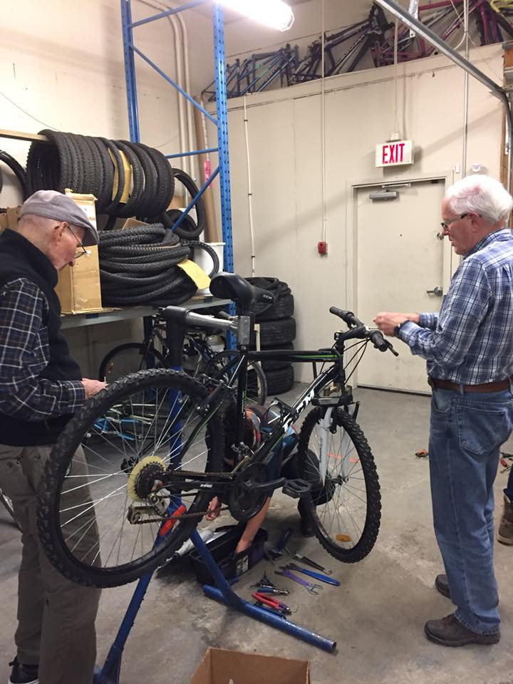 Two older men helping a younger man to fix a bike