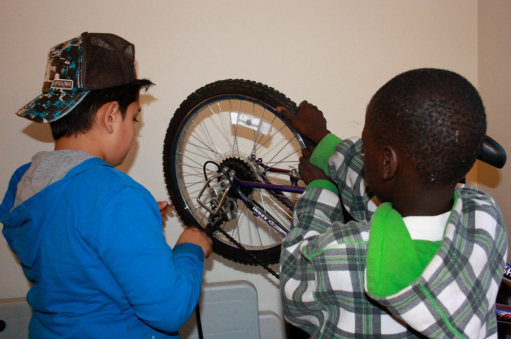Two young people fixing a bicycle
