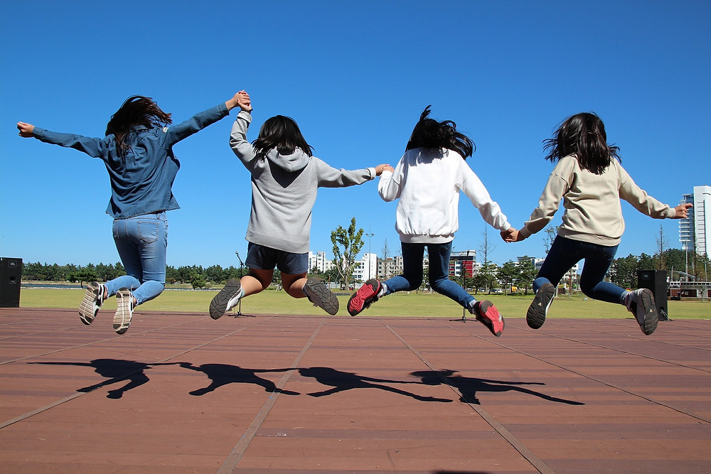 4 girls jumping in the air while holding hands