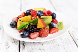 Delicious fruits salad in plate on table