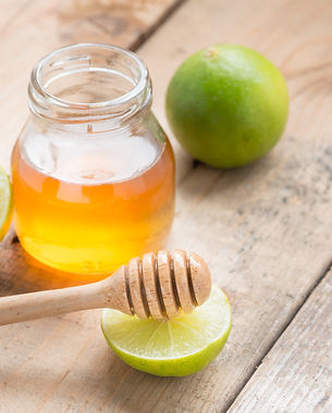 Honey dipper with honey and lime on wood
