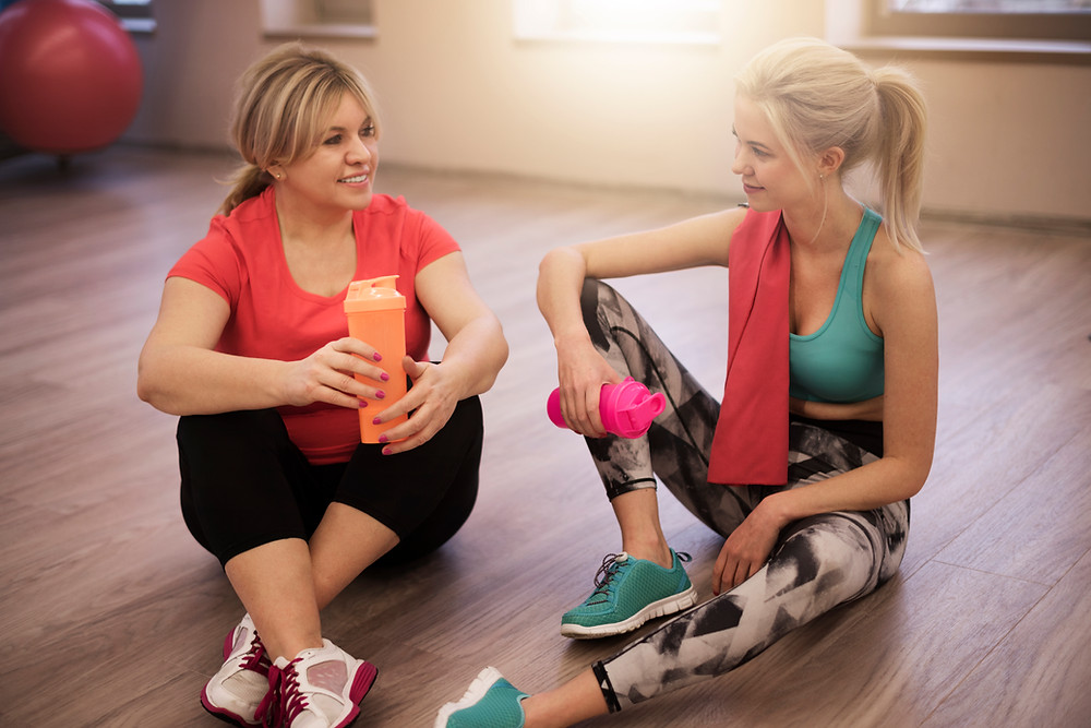 two women in workout clothes sitting on gym floor and talking