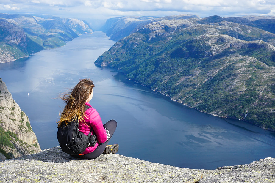 Young woman with long hair and backpack admiring the fjord view (Lysefjord) sitting on the