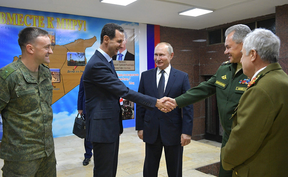 Vladimir Putin shakes hands with the Russian defence minister on a visit to Syria in January 2020