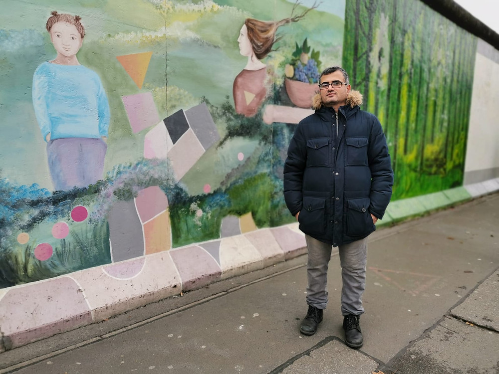 Abu Artema stands in front of a mural on the Berlin wall