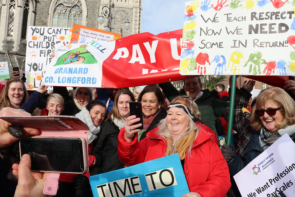 Sinn Féin President Mary Lou McDonald pictured among a crowd of protesters holding placards calling for better pay for early years educators