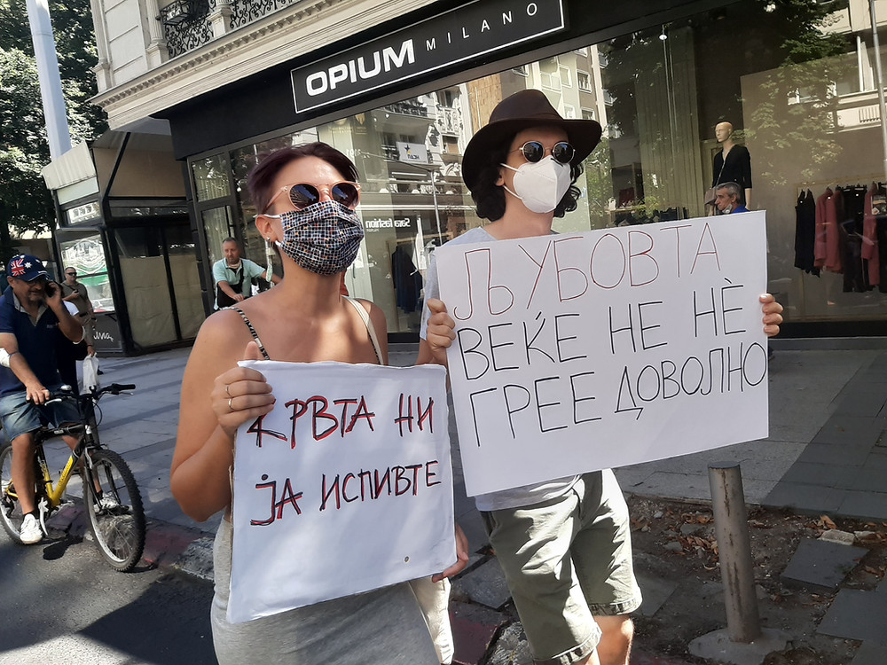 Two people wearing masks carry placards along a city shopping street