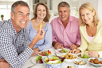 Mid age couples enjoying meal at home.jp