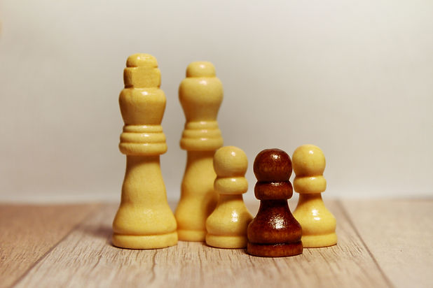 Chess pieces with one a different color.