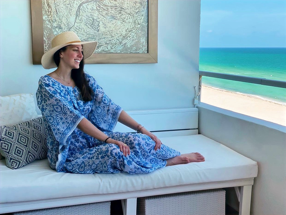 Lindsay Barrasse wearing a YaLiving kaftan sitting comfortably on a patio overlooking the clear blue ocean water of Miami Beach.