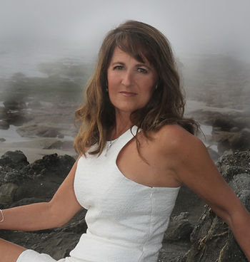 Tina Buenzli, rocks, beach, ocean, white dress, skin cancer, melanoma, autoimmune disease, cancer free, healed from cancer, stage iv skin cancer