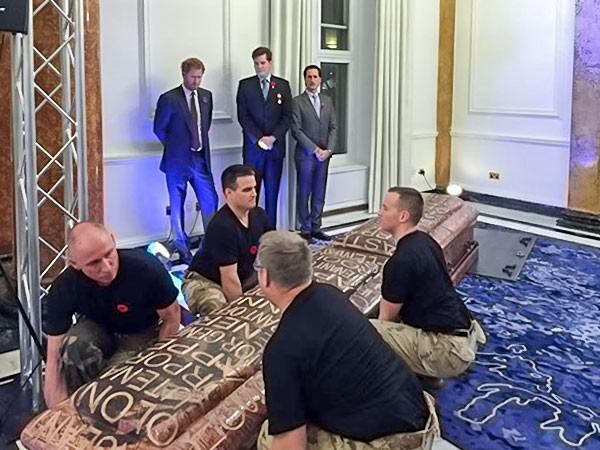 HRH Prince Harry looks on as veterans raise a tribute pole at Canada House in London.