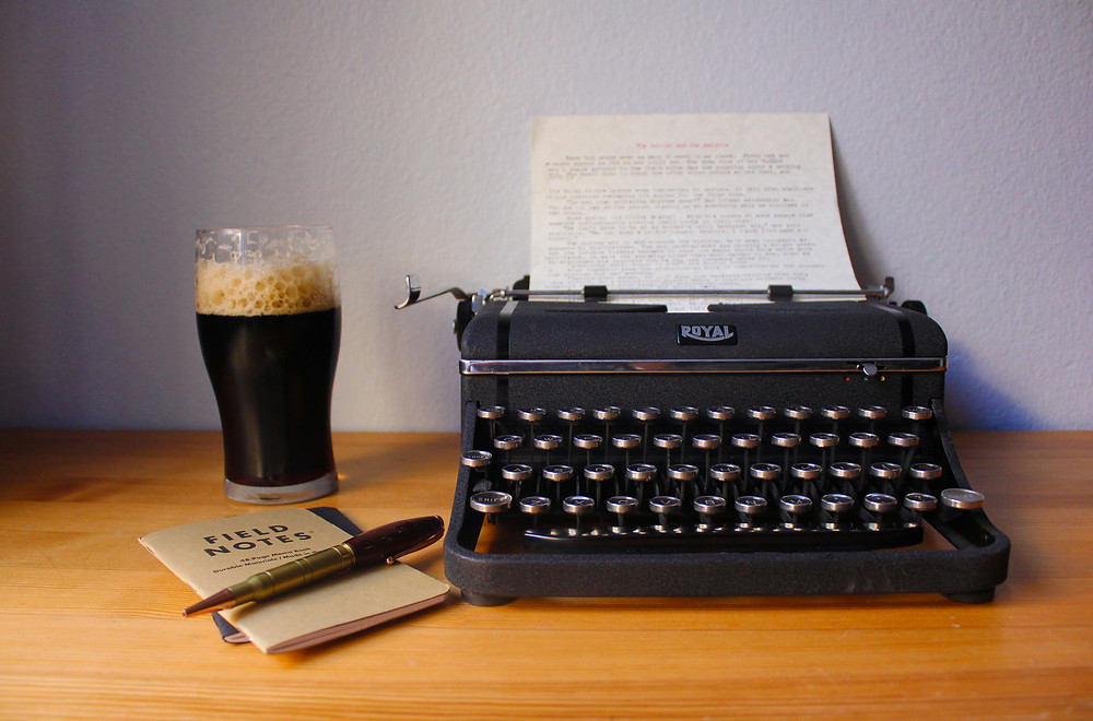 Typewriter, notebook and a pint