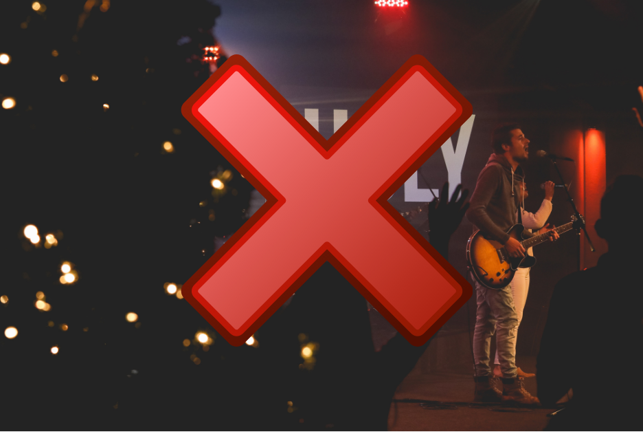 A band are playing near a christmas tree with a large red X over the top.