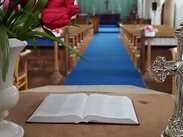 Inside St Elisabeth's Church- view of the aisle and altar with an open bible in the foreground