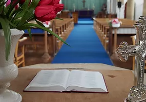 Inside St Elisabeth's - aisle and altar, with an open bible in the foreground