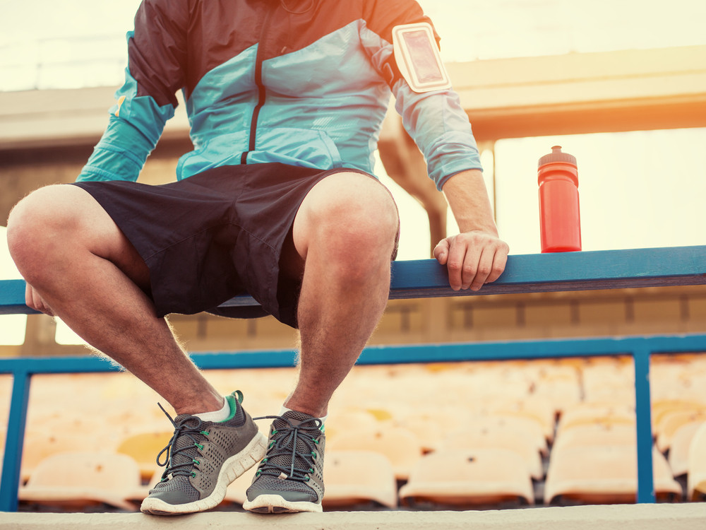 Runner resting on bench with sports energy drink