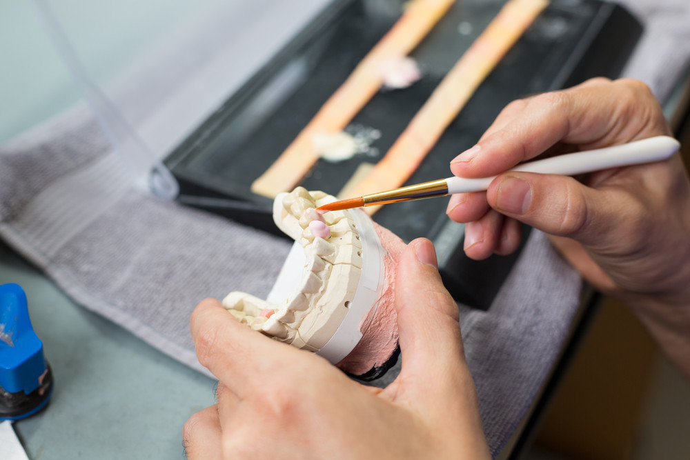 Dental technician crafting dental bridge