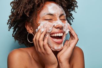 Cheerful black female model applies foam