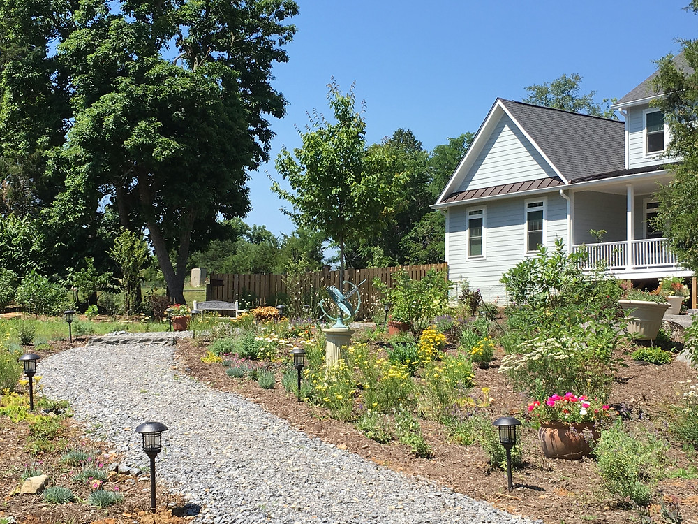 gravel walkway with perennial flowers leading to the front entrance