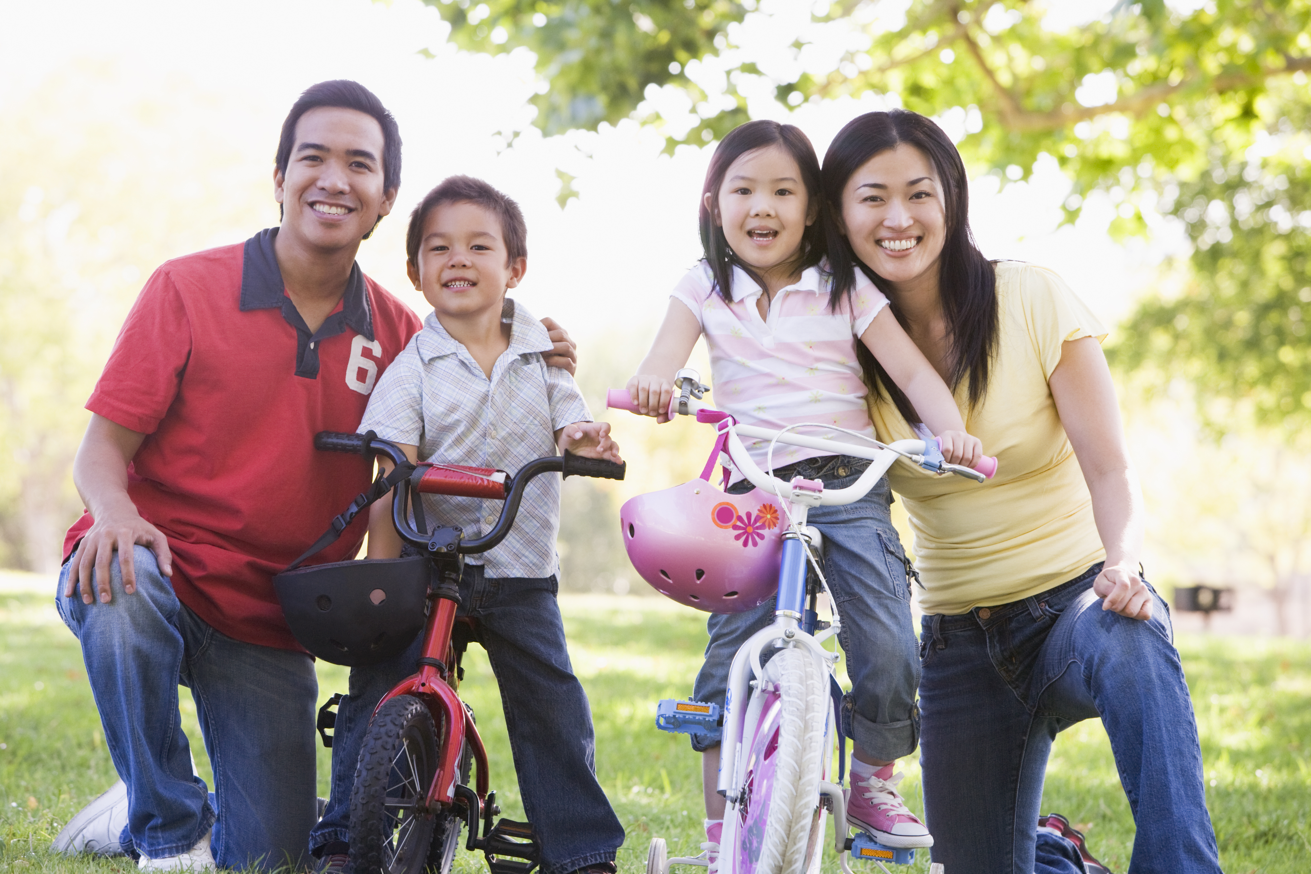 family-with-children-on-bikes-outdoors-smiling_BFGoOtCro