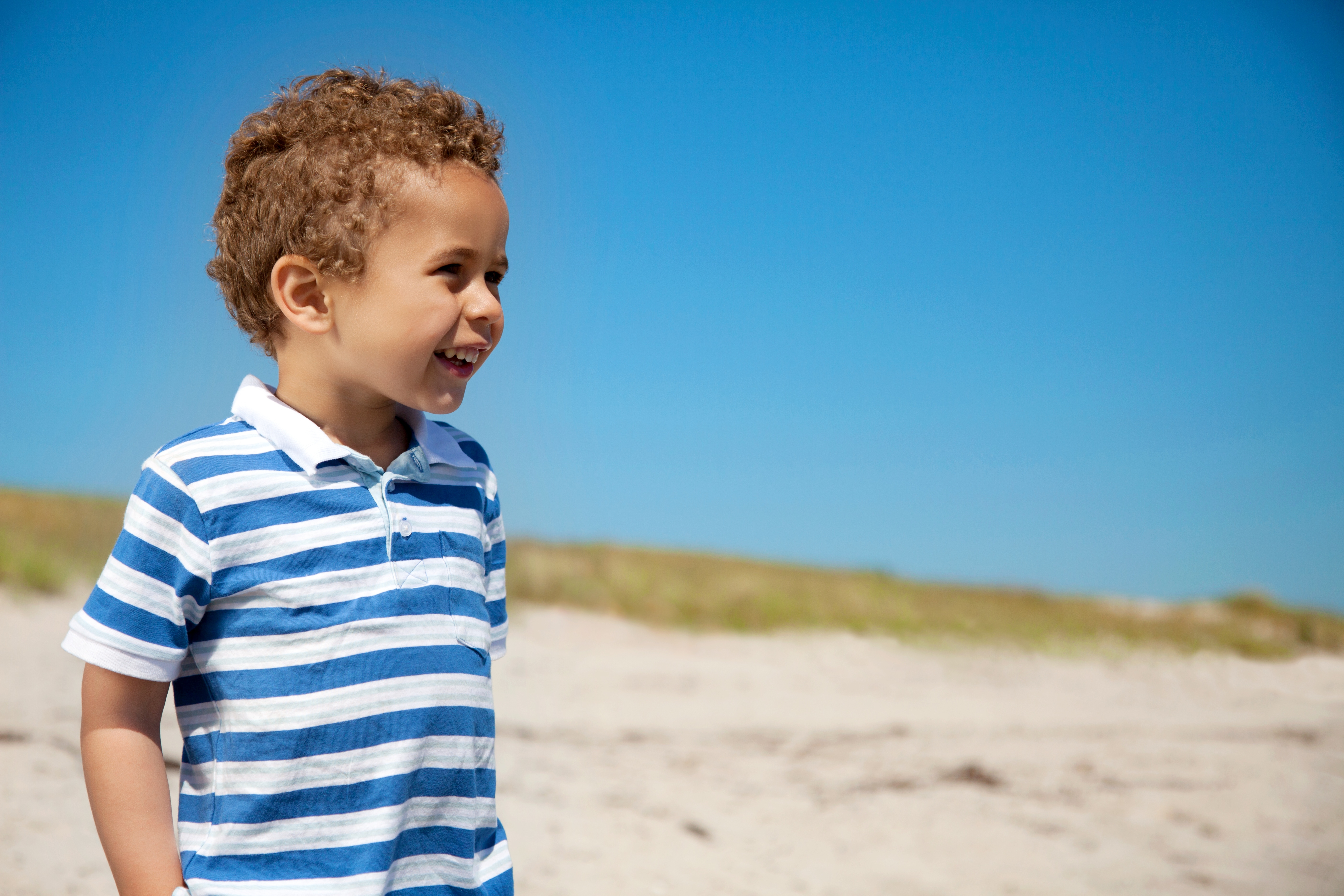 adorable-little-boy-enjoying-the-outdoors-against-the-blue-sky_r6Fw0BEKg