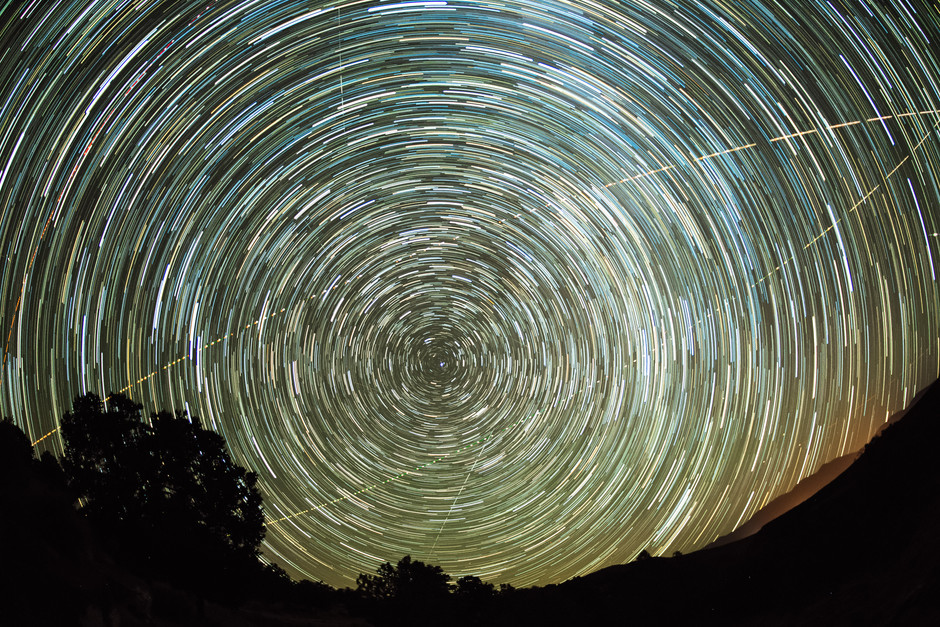 Star trail image of the apparent motion of the stars in around the north star as air planes fly by.