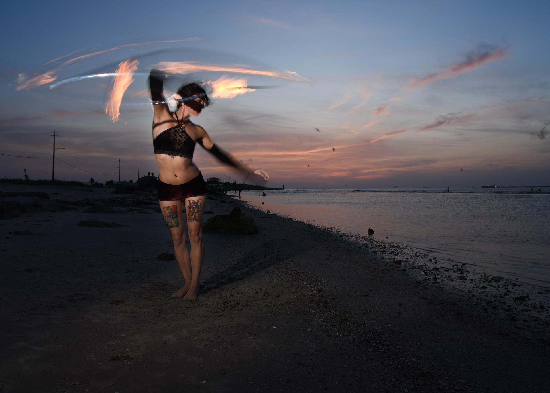 Thalia Patrinos dancing with fire on Galveston beach.