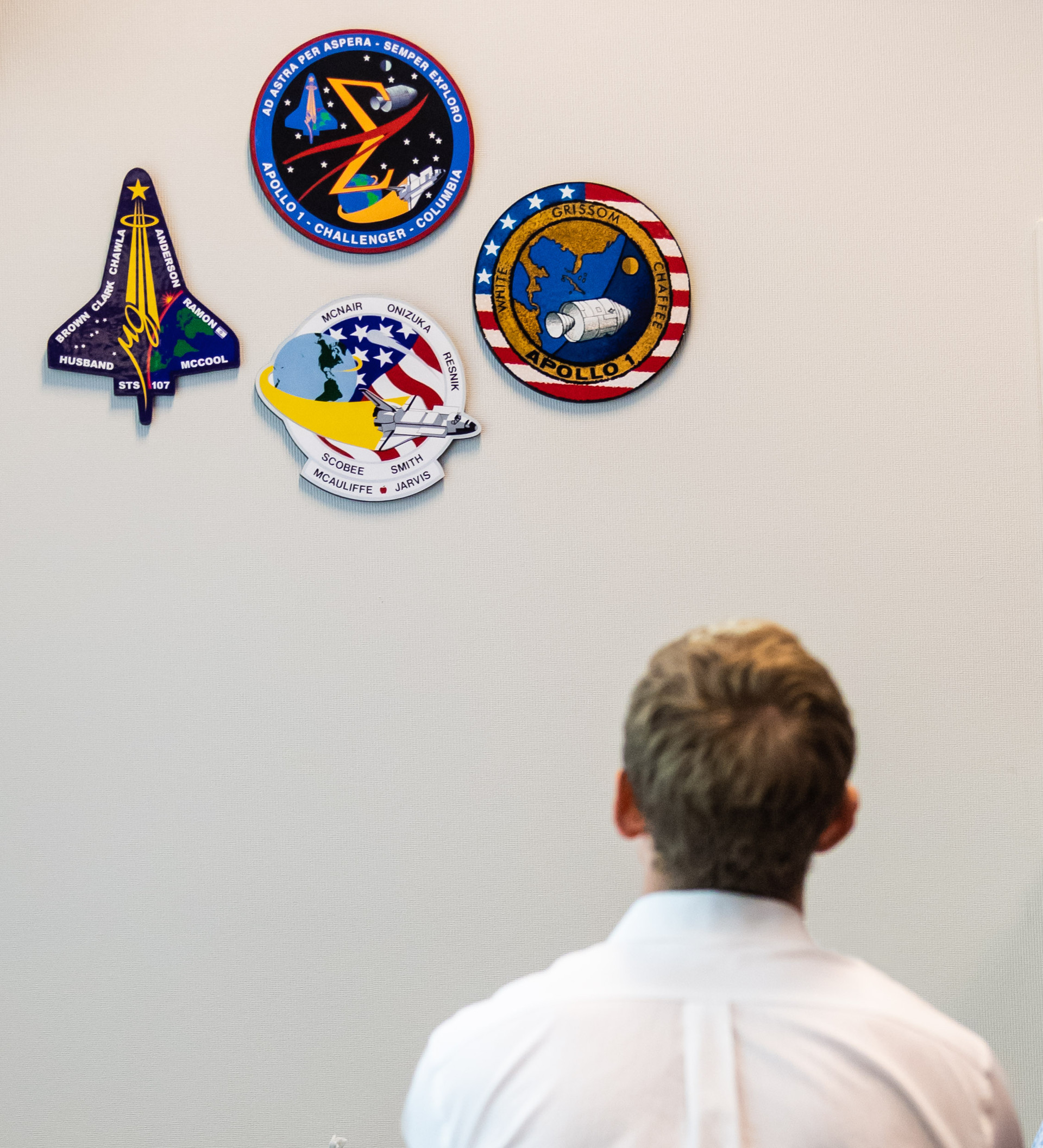 Woody Hoburg observes the Apollo 1, Challanger, and Columbia mission patches that hang on the wall in every mission control room during the 2017 ASCAN tour of MCC.