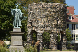 The tower is located in Newport, Rhode Island, behind a fence in grassy Touro Park.