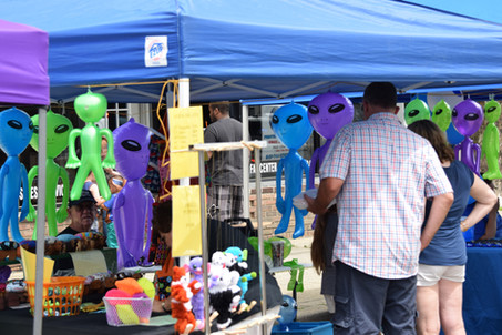 Vendors, crafters, and indie-artists set up tables and tents on Main Street to sell alien-themed swag.