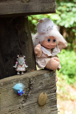 Dozens of plastic, frizzy-haired creatures were nailed and glued to the mouldy wood.
