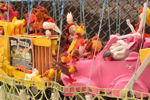 The chickens jumped down on the hood of the pink convertable that crashed into the truck, breaking the cages.