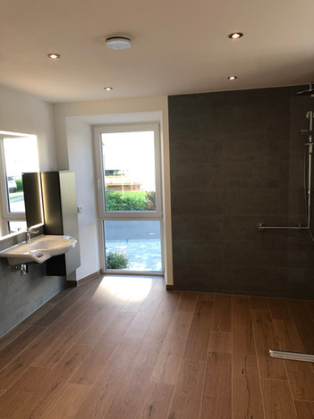 Bodentiefe Fenster (mit Plisses) sorgen für Helligkeit im Bad