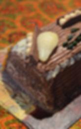 Buche de Noël : biscuit joconde, mousse de poire à la benoîte urbaine et ganache chocolat, coeur croustillant praliné.